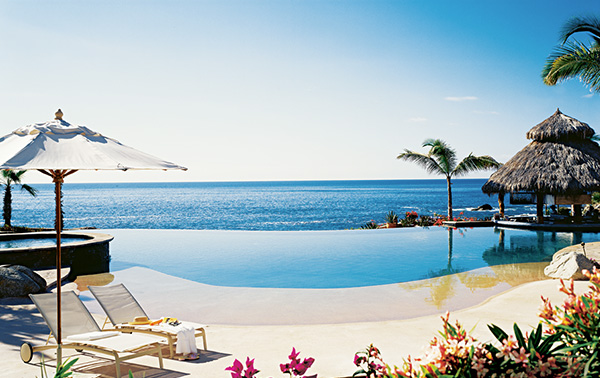 An infinity pool overlooks a glittering ocean view on a clear day.
