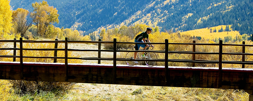 A Dancing Bear Aspen fractional owner bikes over a bridge on a gorgeous autumn day.
