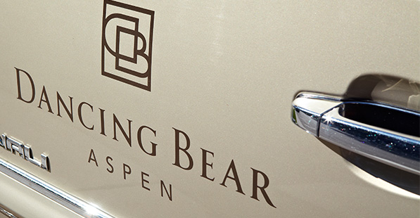 The Dancing Bear Aspen logo appears painted on a car door.