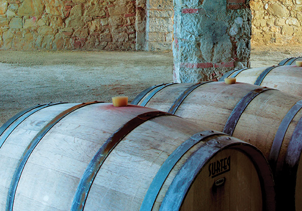 Wooden barrels of wine age in the cellar of a luxury property.