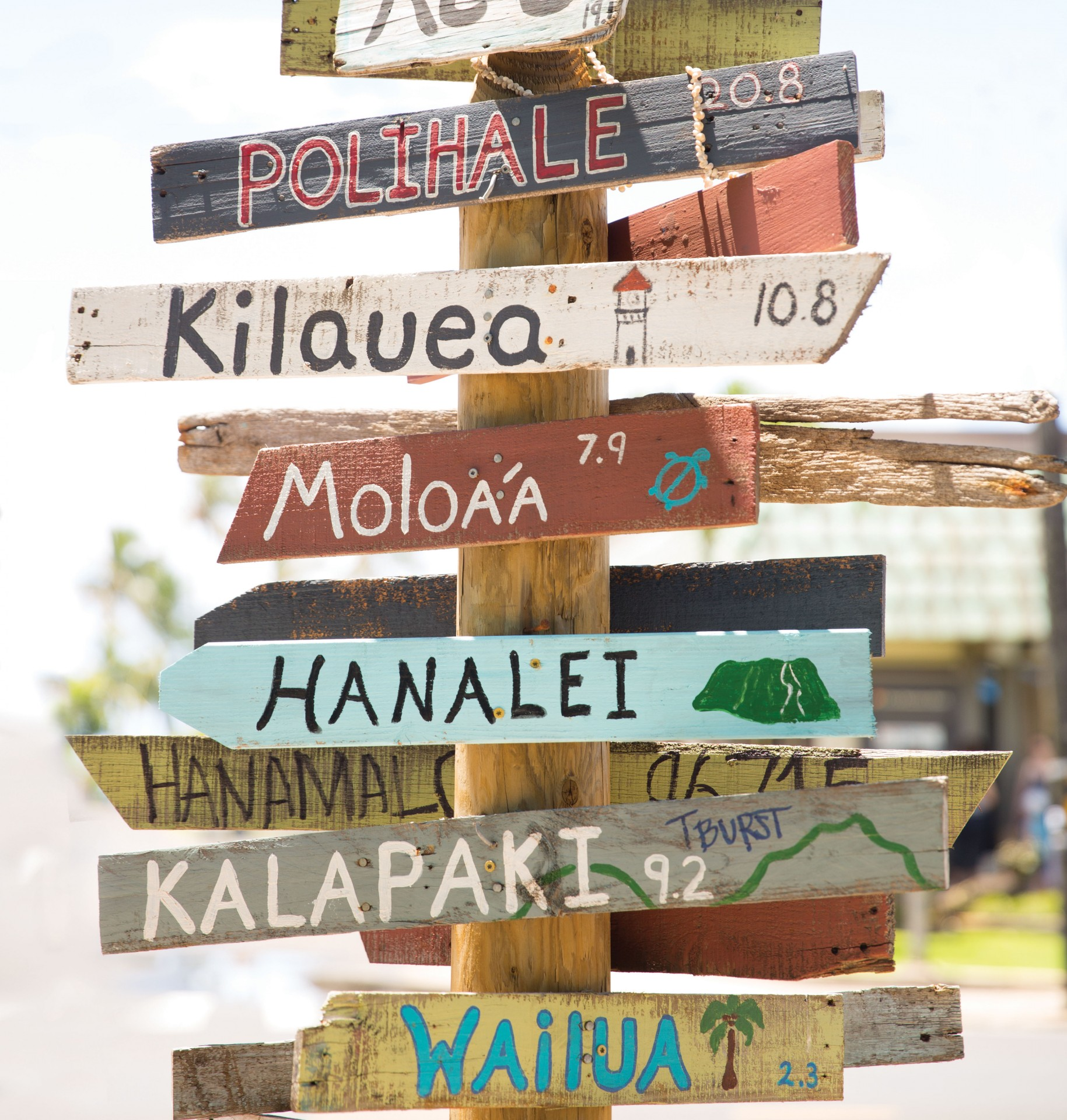 Vintage wooden sign post in Hawaii points the way to different beaches.