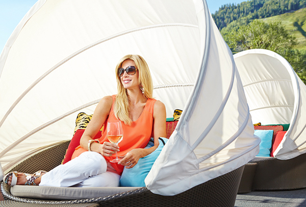 A beautiful blonde woman sits outside in luxury on a designer lounge chair.