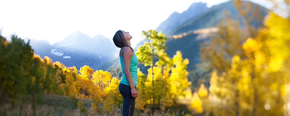 A pretty hiker takes a deep breathe standing atop the Aspen mountains.