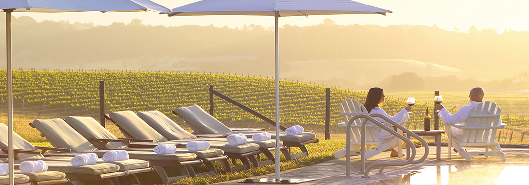 A loving couple sit on lounge chairs and look out over wine vineyards.