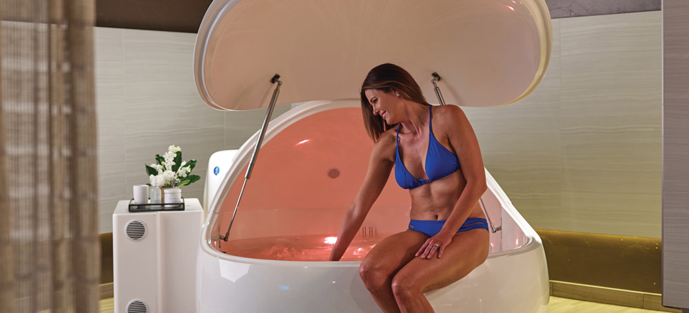 A woman enters a grotton isometric pod to rest and relax at the spa.